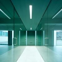Umnutzung eines Fabrikgebäudes zu Büros. Fast alle Wände sind dieses Bürogebäudes sind aus 12 mm starkem grün schimmerndem Sicherheitsglas gebaut