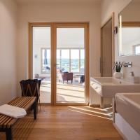Badezimmer mit Blick in den Wohnbereich und Dachterrasse eines Mehrfamilienhauses