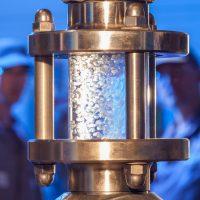 Frisch abgeschlagenes Granulat wird von zwei Mitarbeitern im Schauglas kontrolliert.